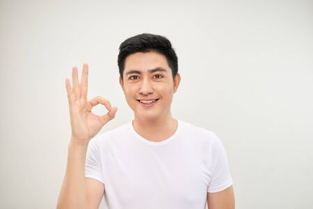 portrait of an asian man doing the okay gesture