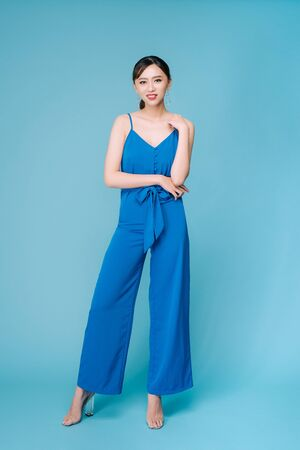 Young beautiful woman posing in new casual blue fashion costume dress with pants full body on blue background Stock Photo - 127705864