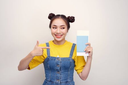 Attractive excited woman 20s smiling while holding passport with travel tickets isolated over white background