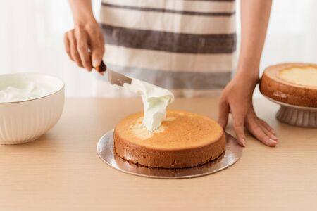 Making of Sponge Cake. Hand putting icing on freshly baked cake on wood table