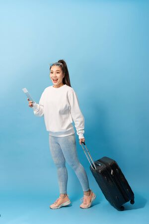 Portrait of trendy young girl standing with suitcase and holding passport with tickets, over blue background Stockfoto