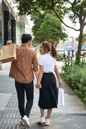 Young happy couple with shopping bags in the city.