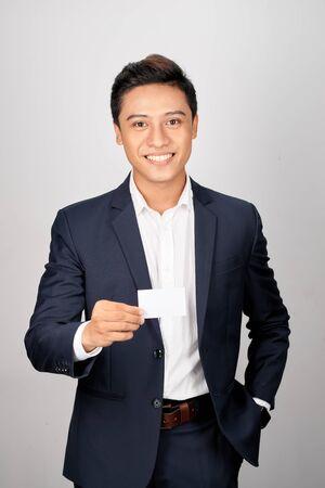 Asiatischer junger Geschäftsmann hält mit Namenskarte