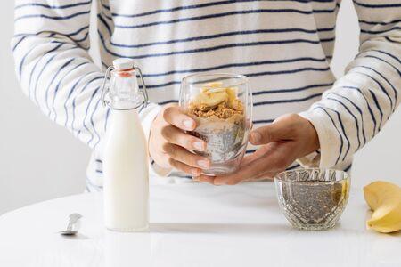 Healthy breakfast with yogurt, nut, banana and chia seeds. Bowl of fresh fruit.