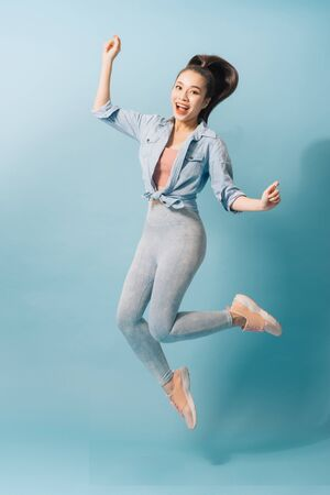 Full length portrait of a joyful young woman jumping and celebrating over light blue background