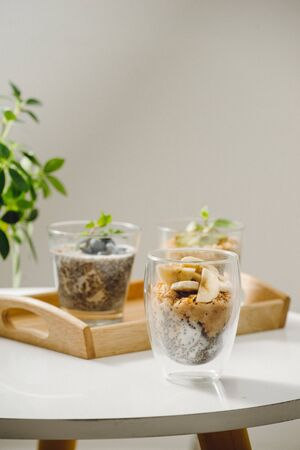 Fruits yogurt parfait with granola and chia seeds for healthy breakfast on wooden table Фото со стока