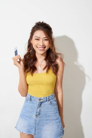 Asian young woman holing card to shopping on white background Фото со стока - 127710788