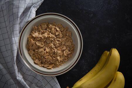 Organic healthy oatmeal porridge with fresh bananas. The white porcelain bowl with napkin Reklamní fotografie