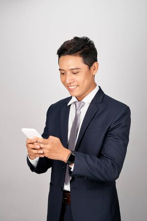 Happy young businessman texting to his colleague, friends, clients Stock Photo