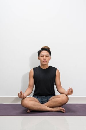 Young black man practicing yoga lesson with instructor, sitting in Sukhasana exercise