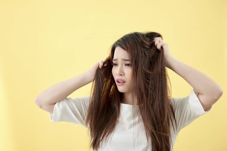 Beautiful attractive young asian woman looking in damage dry hairs feeling so sad and worry, Isolated on white background, Haircare concept Foto de archivo - 127845978