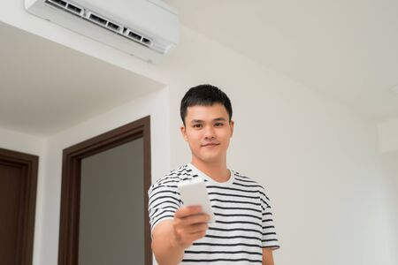 Air conditioner inside unit with man operating remote controller.  Air conditioner with remote controller 写真素材