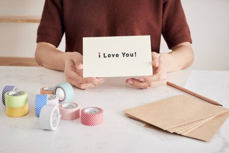hands holding greeting card with phrase letters i love you prepared for sweetheart