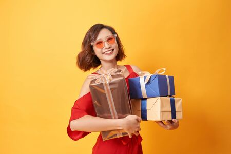 Portrait of casual young happy smiling woman hold gift box. 免版税图像