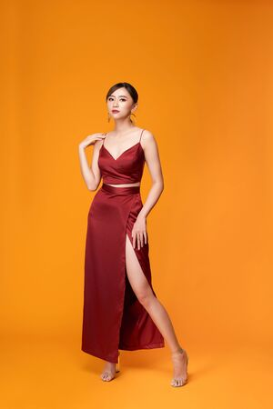 Fashion shot of the elegant woman in beautiful long dress posing in motion Stock Photo