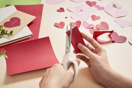 woman cuts out red felt hearts, homemade crafts for Valentines day, hand made creativity, top view