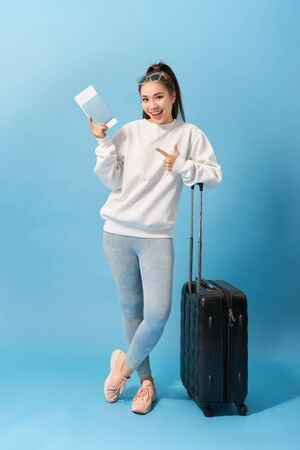 Full length image of Cheerful woman wearing in casual clothing preparing to trip with baggage and tickets over blue background