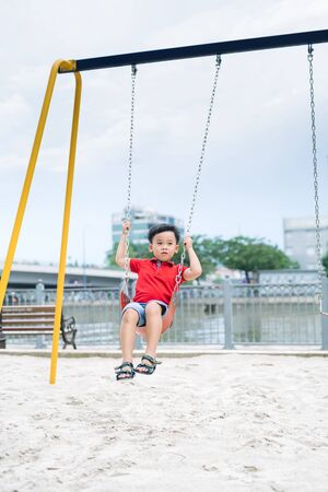 Happy asian boy swinging at the playground in the park Stock Photo