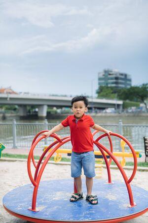 Petit garçon asiatique chevauchant une balançoire et se réjouit