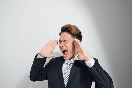 asian young business man in classic black suit shouting out loud 写真素材