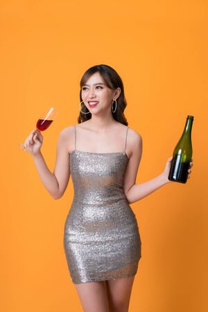 Gorgeous festive young asian woman having a glass of wine.