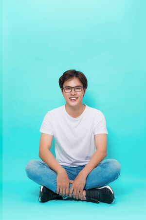young casual asian man sitting on the floor with his legs crossed and smiling for the camera. on blue background