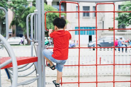 little boy playing on monkey bars at playground Banque d'images - 127846327