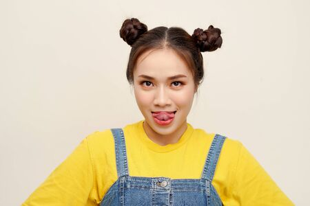 Beautiful young Asian girl wearing jeans dungaree with two buns hair on white background Stock Photo