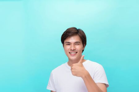 Young optimistic man isolated on blue background showing thump up with positive emotions of content and happiness. Concept of satisfaction with quality and recommendation Stock Photo - 127846429