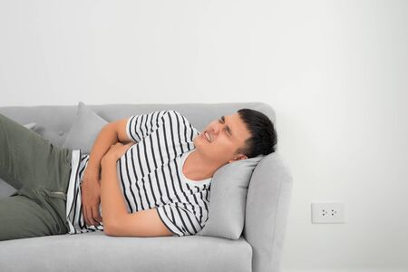 Terrible stomachache. Frustrated handsome young man hugging his belly and keeping eyes closed while lying on the couch at home
