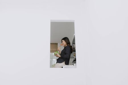 Healthy diet. Beautiful smiling woman eating fresh organic salad in modern kitchen. Healthy eating, food and lifestyle concept. Health, beauty, dieting concept.