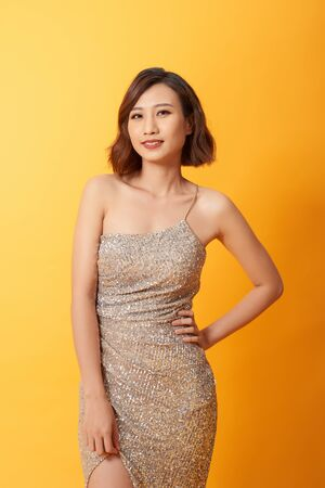 Beautiful female posing in long golden party dress over yellow background Stock Photo
