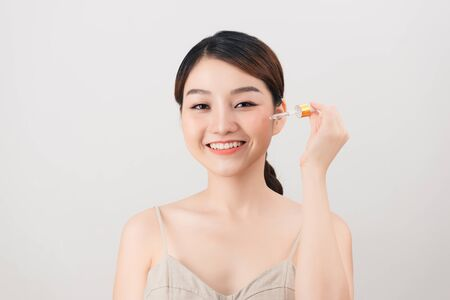 Jonge mooie vrouw die speciale huidbehandeling krijgt bij schoonheidssalon. Mooi meisje dat oogserum aanbrengt Stockfoto