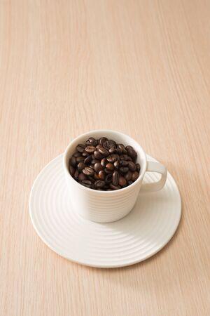 Tasse volle Kaffeebohnen auf dem Holzhintergrund Standard-Bild