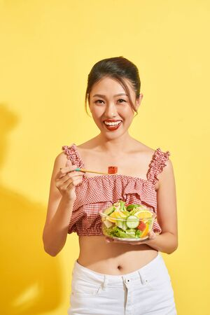 young Asian woman smiling and holding vegetable and salad on yellow background Stock Photo