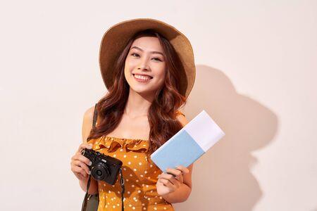 Porträt einer glücklichen jungen Frau mit Hut, die Kamera hält und Reisepass zeigt, während sie einzeln auf beigem Hintergrund steht