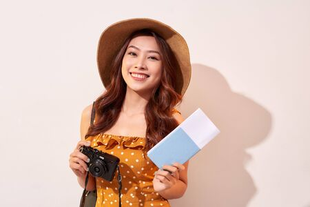 Portrait of a happy young woman in hat holding camera and showing passport while standing isolated over beige background
