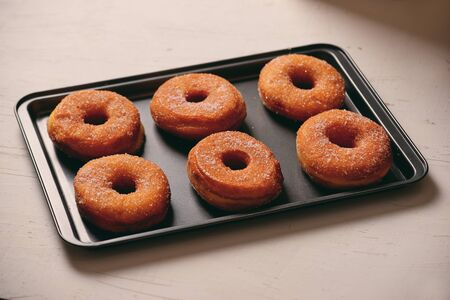 Fried Donuts with Powdered Sugar on metal baking dish