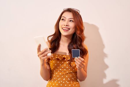 Portrait of a happy girl holding mobile phone and a credit card isolated over biege background