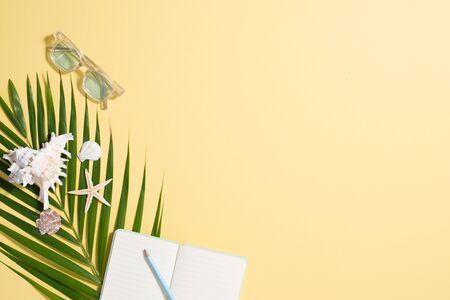 Colorful summer holidays fashion flat lay - straw hat, sunglasses, sea shells on bright yellow background 版權商用圖片