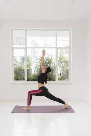 Young sporty woman practicing yoga near the window,
