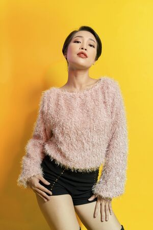 Adorable woman expressing true positive emotions during photoshoot in pink fur coat. Indoor portrait of active glamorous girl standing in confident pose and smiling.
