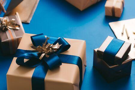 Scatola d'oro con nastro azzurro su sfondo blu. Concetto di Natale