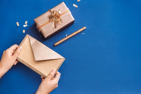 Writing Christmas wishes with gold box and wreath on blue background Stockfoto