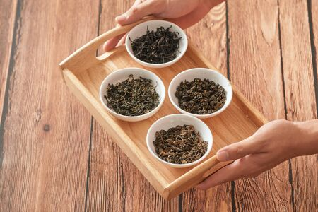 The tray on hands with white bowls of dry teas leaves