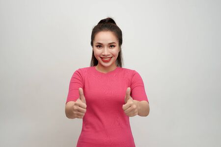 Enthusiastic motivated attractive young woman giving a thumbs up gesture of approval and success with a beaming smile 写真素材 - 129273237