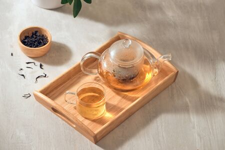 Tea in a transparent cup and teapot on a wooden background Фото со стока