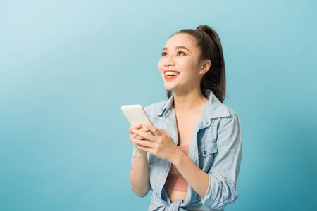 Asian woman 20s holding mobile phone and smiling over blue background 免版税图像 - 128768424