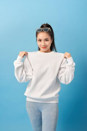 Girl showing new t-shirt she bought on sale, being pleased and happy over light blue background Banque d'images - 128926283
