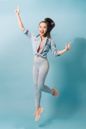 Portrait of playful crazy girl jumping in the air looking at camera enjoying weekend having perfect mood on light blue background Banco de Imagens - 129033677